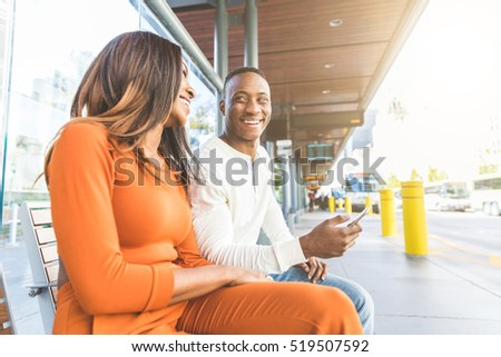 Black couple waiting for the bus at station. Man and woman sitting on a bench and looking each other, smiling. He is looking at bus timetable on the phone.