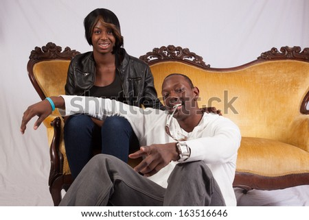 Black couple with the woman sitting on a couch and the  man sitting on the floor with his arm across her knees