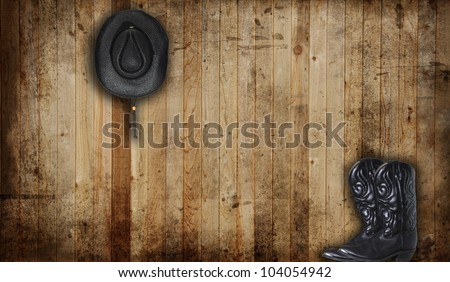 Black Cowboy boots and hat against a weathered cedar background panel. - stock photo