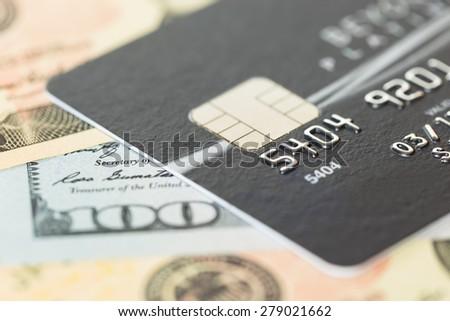 Black credit card on dollar banknote - stock photo