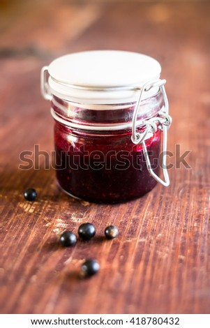 Black currant confiture or jam in a jar on a wooden table, selective focus - stock photo