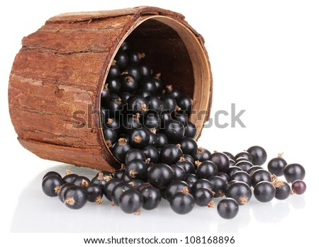 Black currant in wooden cup isolated on white - stock photo