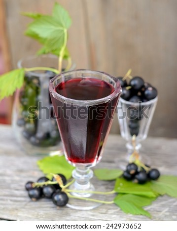 black currant liquor and ripe berries  on  wooden table. Selective focus - stock photo