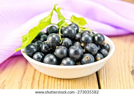 Black currants in a white bowl with green leaves, purple cloth on a wooden boards background - stock photo
