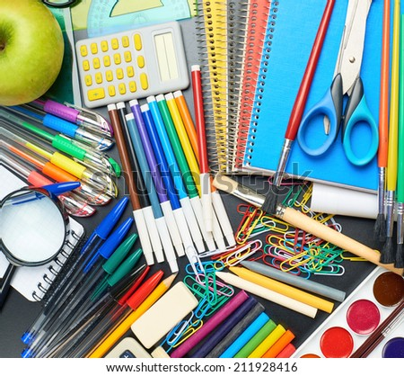 Black desk's surface covered with multiple stationery office supplies as a background back to school composition, top view above - stock photo
