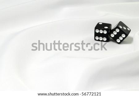 Black dice on white fabric - stock photo