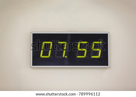 Black digital clock on a white background showing time 7 hours 55 minutes A digital alarm natural reflection
