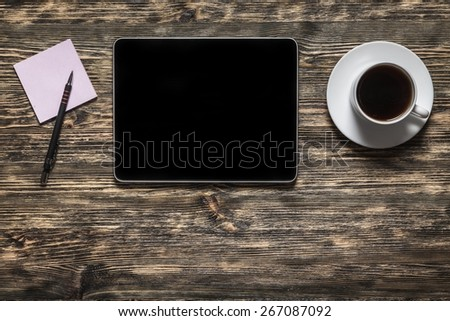 Black. Digital tablet computer with sticky note paper and cup of coffee on old wooden desk. Simple workspace or coffee break with web surfing. - stock photo