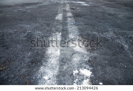 Black dirty asphalt with white lines - stock photo