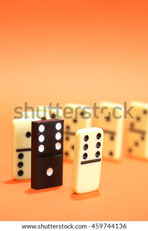 Black domino among white dominoes standing in a row on red background