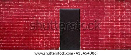 Black Door and Red Brick Wall - stock photo