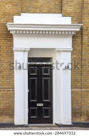 Black door and yeelow brick wall in London - stock photo