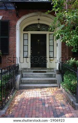 Black door in Boston on a stately brownstone in the beacon hill area. With a brick walkway and wrought iron fence and a fox head door knocker. - stock photo