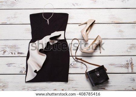 Black dress and retro purse. Dark retro bag on showcase. Lady's evening look with accessories. Outfit with jewelry and handbag. - stock photo