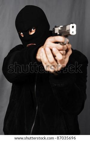 black dressed man and gun in studio - stock photo