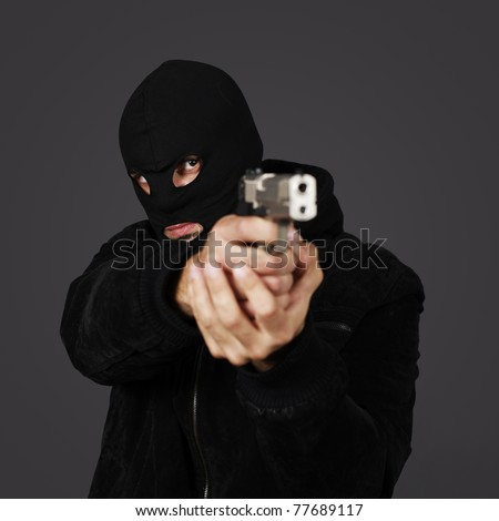 black dressed man with gun in studio - stock photo