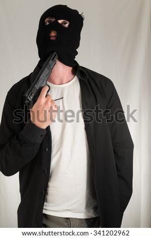 Black Dressed Young Man Holding a Pistol Gun - stock photo