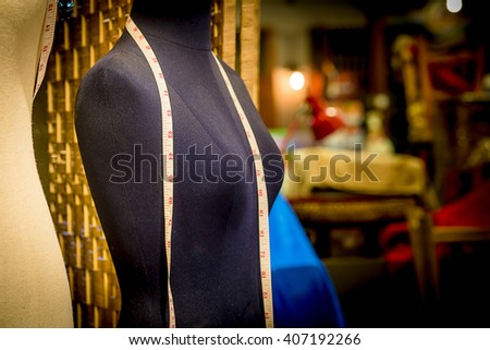 Black dummy with measuring tape in tailors studio - stock photo