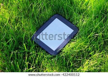 Black E-book lays on green grass - stock photo