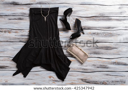 Black evening dress and heels. Silver clutch bag with dress. Woman's dark outfit with jewelry. Quality clothes and precious accessory. - stock photo