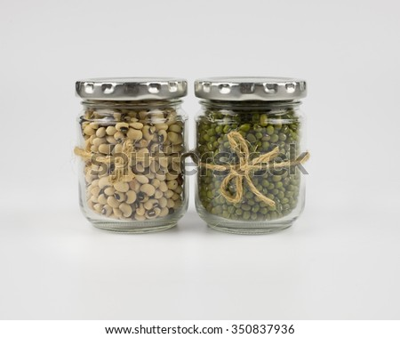 Black eye peas and mung beans in a mason jar over white background - stock photo