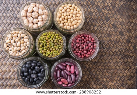 Black eye peas, chickpeas, adzuki beans, mung bean, soy beans, black beans and red kidney beans in mason jars on wicker tray - stock photo