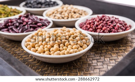 Black eye peas, mung bean, adzuki beans, soy beans, black beans and red kidney beans in white bowl on wicker tray