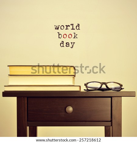 black eyeglasses and some books on a table and the sentence world book day on a beige background, with a retro effect - stock photo