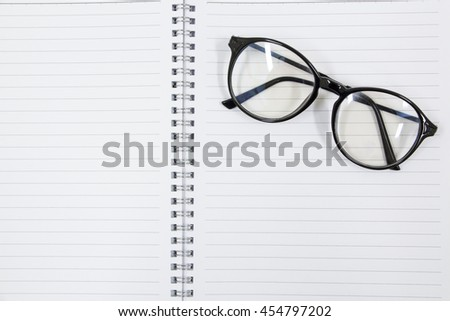 Black eyeglasses with placed on top of an empty notebook page