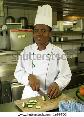 Black female chef is cutting zucchini on the cutting board