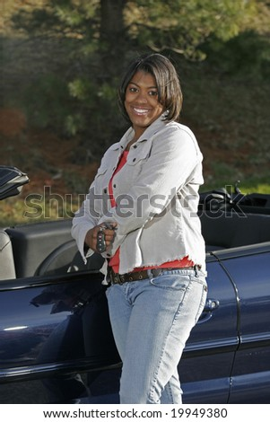 black female teen driver standing with new car - stock photo