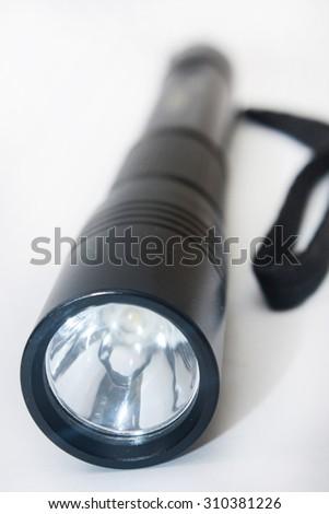 Black flashlight on the white background. - stock photo