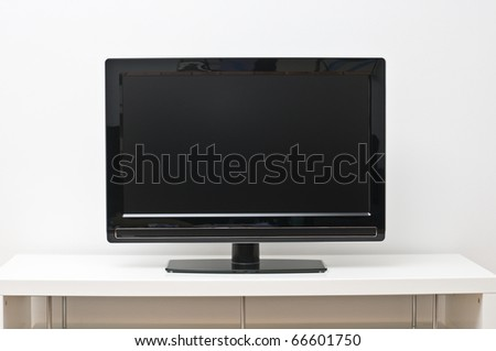 Black flat screen tv set on white table and wall - stock photo