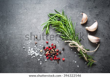 Black food background with olive oil, rosemary and spices, copy space, top view. - stock photo