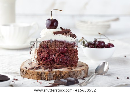 Black forest cake ,decorated with whipped cream and cherries Schwarzwald pie, dark chocolate and cherry dessert on a white wooden background