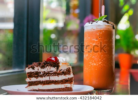 Black Forest Cake decorated with whipped cream and cherries with drinks  - stock photo