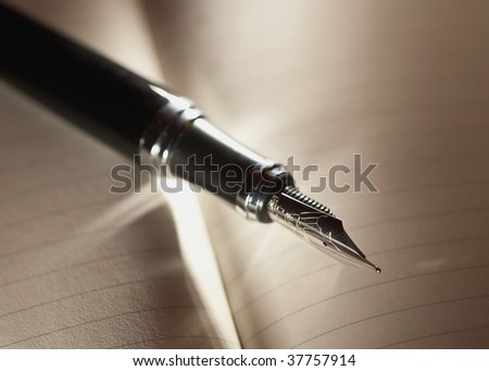 Black fountain pen on notebook with dramatic lighting - stock photo