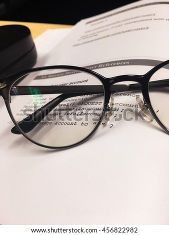 black frame of glasses on the book text and table - can  use to display or montage on products