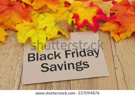 Black Friday Savings Card, Autumn Leaves on weathered grunge wood with a Black Friday Deals  Savings - stock photo