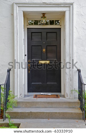 Black front door to white house with newspaper and lamp