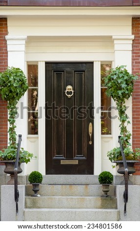 Black Front Door with White Portico and Greenery  - stock photo