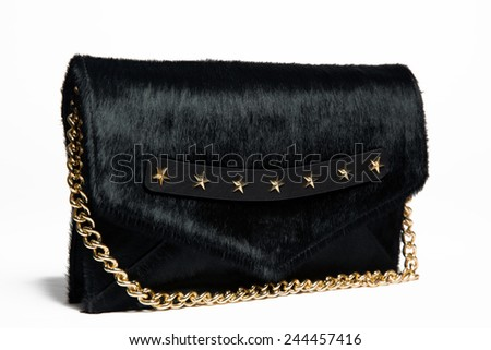 Black fur woman bag with gold stars and chain on white background - stock photo