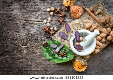 Black Galingale in Mortar Grinder drugs and ingredient herbs on wooden background