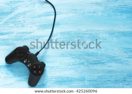 Black Gamepad lies on a blue wooden background. Flat lay - stock photo