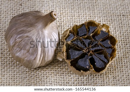 Black garlic bulb with cross section showing black cloves - stock photo