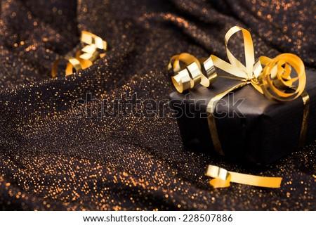 Black gift box on black shiny background. - stock photo