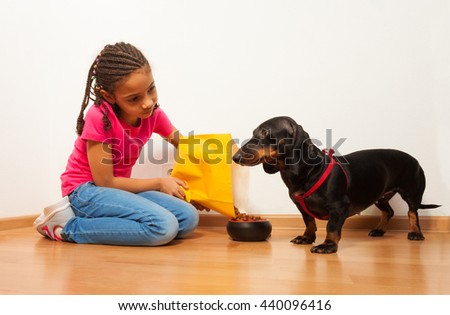 Black girl feed her dog pet with food - stock photo