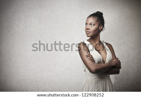 Black girl in white with her arms folded - stock photo