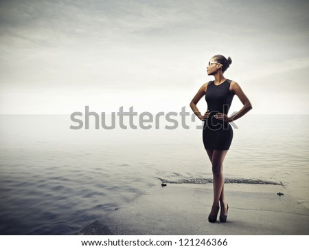 Black girl posing in black on a pier - stock photo