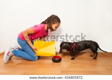 Black girl put food on dog plate - stock photo